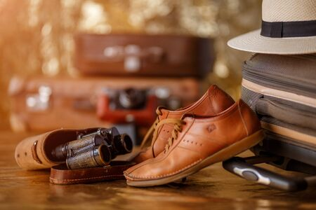 Vintage binoculars and male shoess on suitcase. Shallow depth of field. Travel concept.