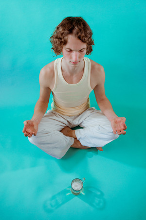 Peaceful young man doing yoga and meditation with mug of beer Foto de archivo