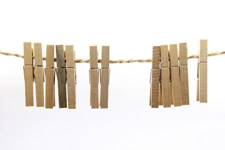 Wooden clothes clips isolated on rope Stock Photo - 14923108