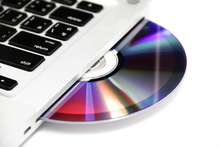 white cd or dvd disk in the drive of a laptop
