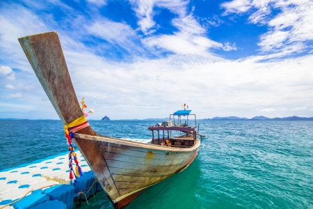 blue dock and longtail boat on andaman sea photo