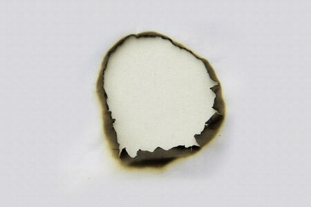 Fire holes in white paper Stock Photo