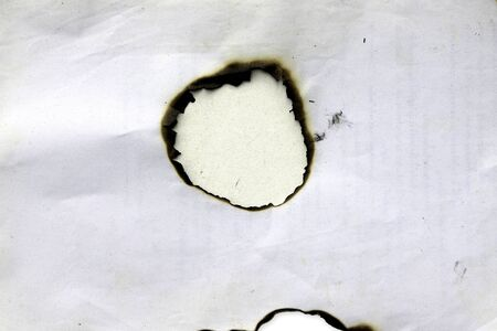 Fire holes in white paper photo