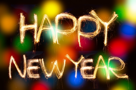 christcross: happy new year written with Sparkling figures  on bokeh background Stock Photo