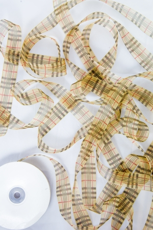 Gold line satin ribbons out from reel Stock Photo - 17469117
