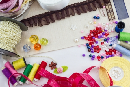 Tools for sewing and handmade  thread, scissors, pins on brown paper Stock Photo - 17469087