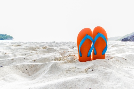 Orange flip-flop on the beach photo