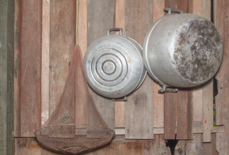 of old times: Old pots hanging on the wooden wall. of an old country house - retro equipment of old times Stock Photo
