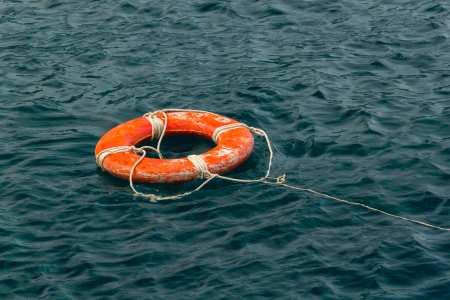Safe water support aid circle with rope. Rescue red life buoy on wooden background of ship or boat. Helpful object. photo