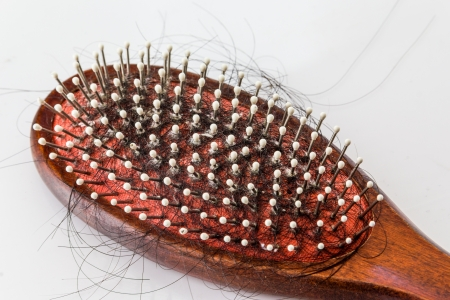 Hair brush with lost hair on it, on white background photo