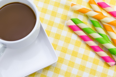 Hot chocolate with Wafer rolls stick in white cup