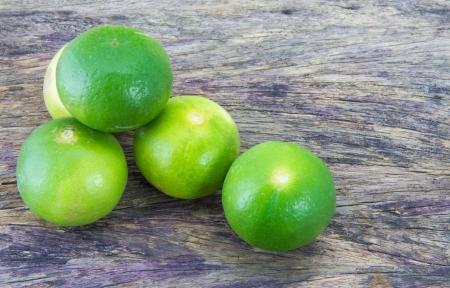 Fresh limes on wood background