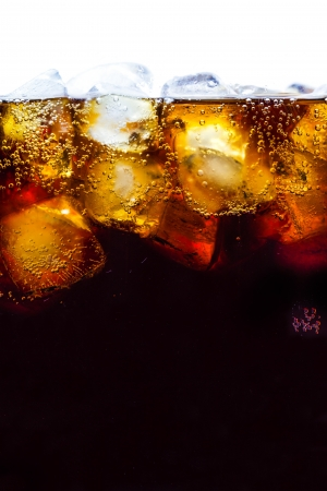 Cola with ice cubes close up background