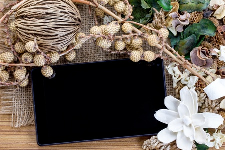 Dry flowers frame on wooden background with tablet computer  tablet pc  photo