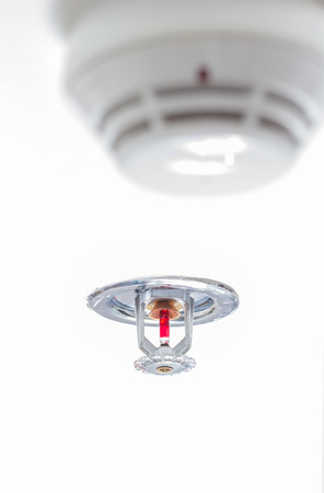 Fire protector and Fire sprinkler on white ceiling as background