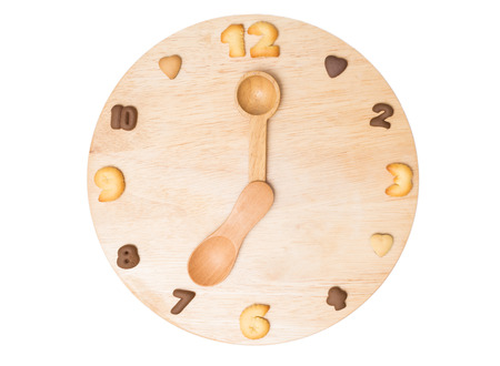 Clock made of wooden spoons on wooden background. eating time concept photo