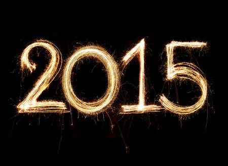 2015 word written with Sparkle firework on black background