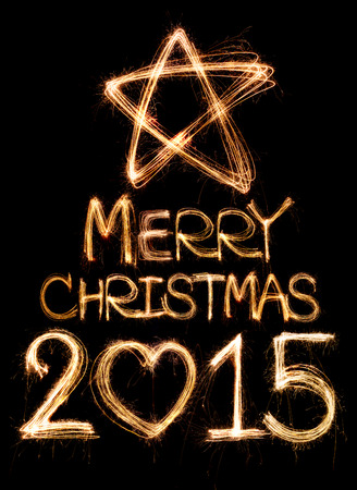 Merry christmas 2015 written with Sparkle firework on black background photo