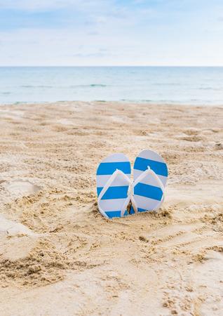 flipflops: Summer vacation concept--blue Flipflops on a sandy ocean beach Stock Photo
