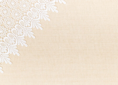 Close up of Lace flowers frame over Fabric design for border or background photo