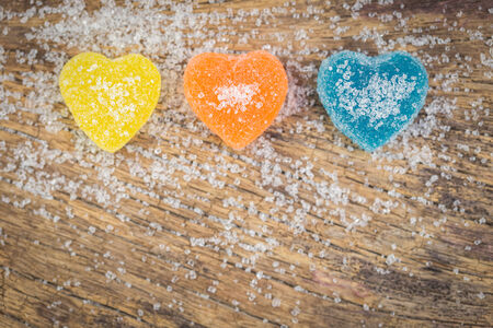 Blue,Orange,Yellow  jelly candies in heart shape with sugar over wooden background texture photo