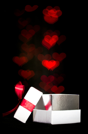 moving out: Defocused red hearts lights are moving out of open gift box Stock Photo