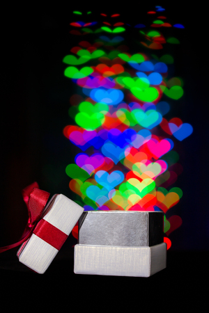 moving out: Defocused hearts lights are moving out of open gift box