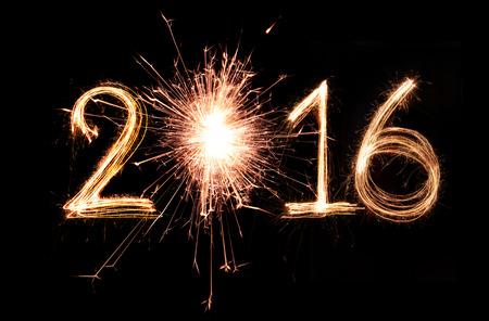 fuegos artificiales: 2016 palabra escrita con el fuego artificial de la chispa en el fondo negro