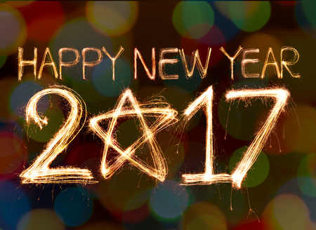 glow pyrotechnics: Happy new year 2017 written with Sparkling  light on bokeh background