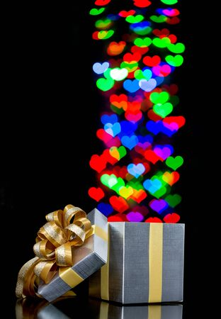 moving out: Defocused bokeh lights heart shaped are moving out of open gift box Stock Photo