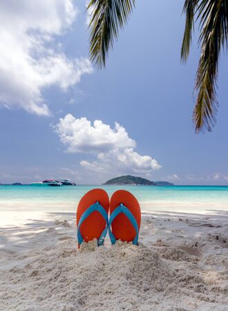 swimming shoes: Summer vacation concept--Orange flip-flop on the white sand beach Stock Photo