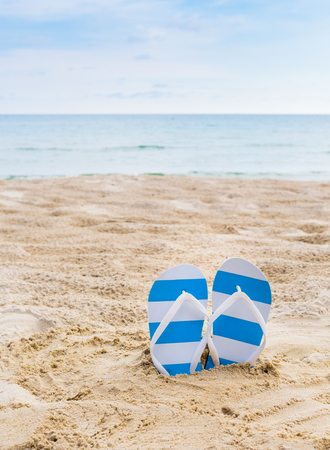 swim shoes: Summer vacation concept--blue Flipflops on a sandy ocean beach Stock Photo