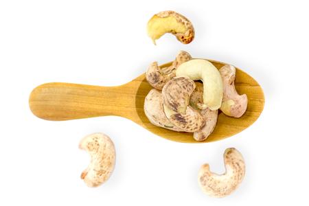cashews: Cashews nut heap in wooden spoon on white background