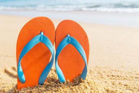 flipflops: Summer vacation concept--Orange Flipflops on a sandy ocean beach