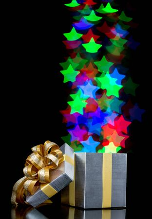 moving out: Defocused bokeh lights star shaped are moving out of open gift box Stock Photo