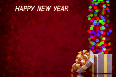 moving out: Happy new year written with Sparkle firework and Defocused lights moving out of open gift box Stock Photo