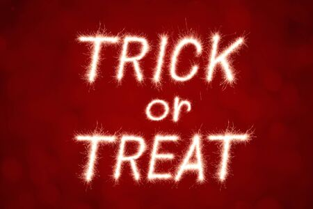 Halloween Message Trick or Treat written with Sparkle firework over red bokeh  background Stock Photo