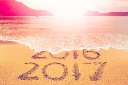 New Year 2017 is coming concept. Happy New Year 2017 replace 2016 concept on the sand beach