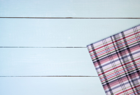 Empty white wooden table covered with checkered tablecloth