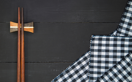Wooden chopsticks over plaid tartan tablecloth on black wooden table in top view