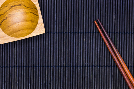 Wooden Sauce bowl and chopsticks on the black bamboo mat background in top view