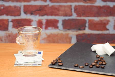 summation: Cup of coffee with bill on brick wall