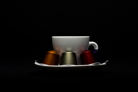 Cup of coffee with capsules on black background