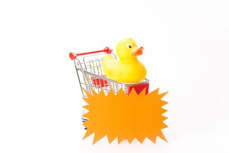 agachado: Caddy para ir de compras con pato sobre fondo blanco Foto de archivo