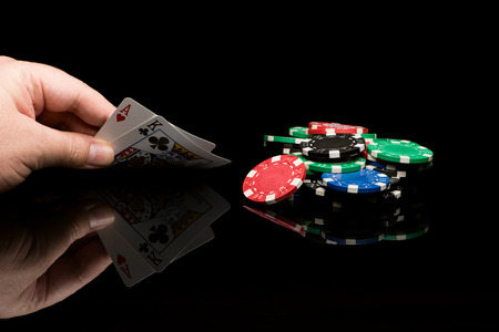 Poker cards with hand on black background with reflexion Standard-Bild