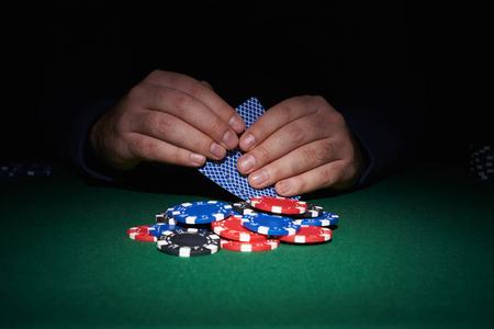 cartas poker: Fichas de póquer en la mesa con las manos y las tarjetas en el casino con fondo negro
