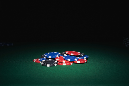 poker: Poker chips on table in casino with black background
