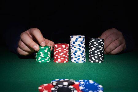 黒い背景とカジノでの手でテーブルの上のポーカー チップ