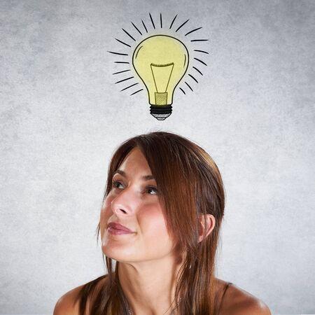 personas pensando: Retrato de la mujer que piensa con la bombilla sobre fondo gris