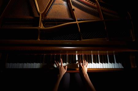 女性の手のクローズ アップの夜のピアノのキーボードを演奏 写真素材